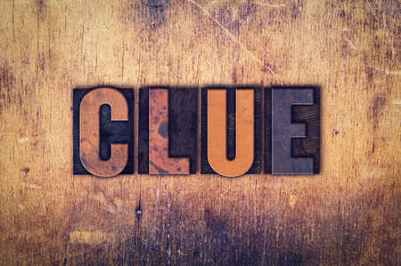 crime solving: The word Clue written in dirty vintage letterpress type on a aged wooden background.