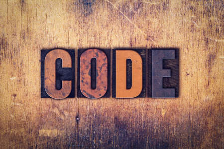 secret code: The word Code written in dirty vintage letterpress type on a aged wooden background. Stock Photo