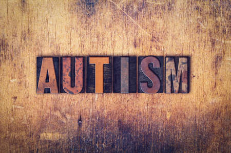 developmental disorder: The word Autism written in dirty vintage letterpress type on a aged wooden background.