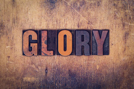 reverent: The word Glory written in dirty vintage letterpress type on a aged wooden background.