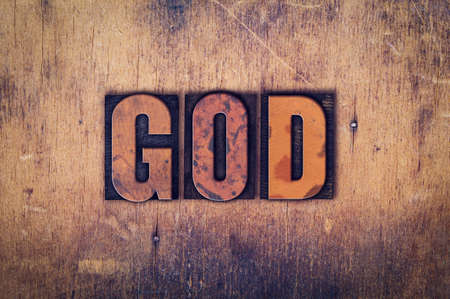 jesus word: The word God written in dirty vintage letterpress type on a aged wooden background. Stock Photo