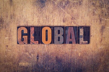 The word Global written in dirty vintage letterpress type on a aged wooden background.