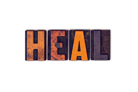 The word Heal written in isolated vintage wooden letterpress type on a white background.