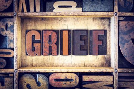 vigil: The word Grief written in vintage wooden letterpress type.
