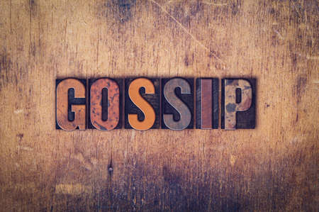 slander: The word Gossip written in dirty vintage letterpress type on a aged wooden background.