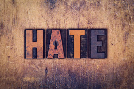 spite: The word Hate written in dirty vintage letterpress type on a aged wooden background.