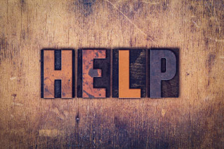 """The word """"Help"""" written in dirty vintage letterpress type on a aged wooden background. Banco de Imagens"""
