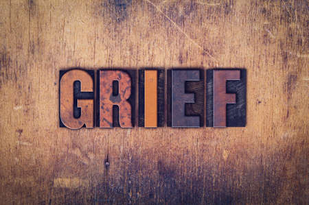 bereavement: The word Grief written in dirty vintage letterpress type on a aged wooden background.