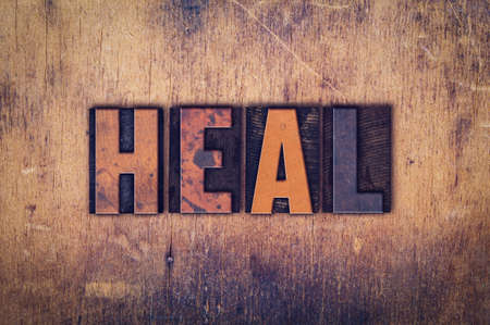 The word Heal written in dirty vintage letterpress type on a aged wooden background. Stock fotó