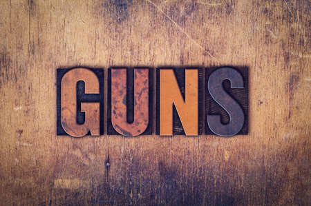 muzzleloader: The word Guns written in dirty vintage letterpress type on a aged wooden background. Stock Photo