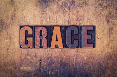 The word Grace written in dirty vintage letterpress type on a aged wooden background.