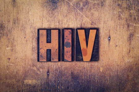 The word HIV written in dirty vintage letterpress type on a aged wooden background.