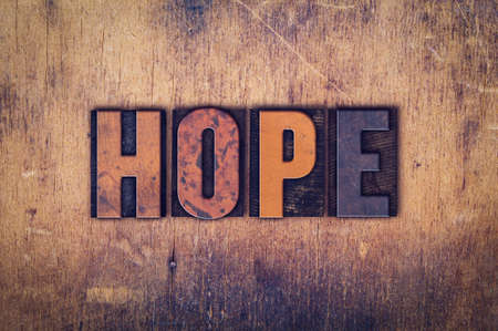 hope: The word Hope written in dirty vintage letterpress type on a aged wooden background.