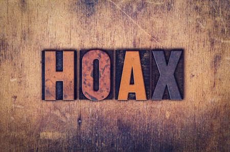 hoax: The word Hoax written in dirty vintage letterpress type on a aged wooden background.