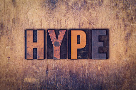 hype: The word Hype written in dirty vintage letterpress type on a aged wooden background.