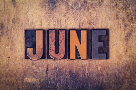 The word June written in dirty vintage letterpress type on a aged wooden background.
