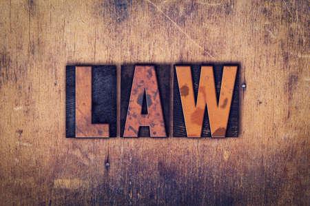 """edicto: La palabra """"ley"""" escrita en el tipo de cosecha sucio en un fondo de madera envejecida."""