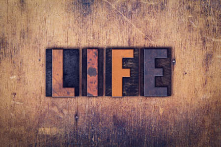 The word Life written in dirty vintage letterpress type on a aged wooden background.
