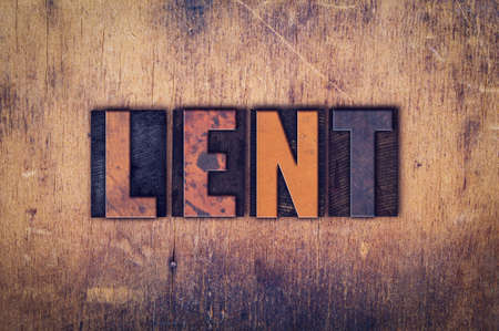 atonement: The word Lent written in dirty vintage letterpress type on a aged wooden background. Stock Photo