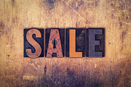 markdown: The word Sale written in dirty vintage letterpress type on a aged wooden background. Stock Photo