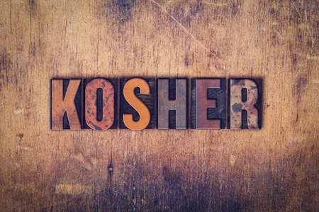 The word Kosher written in dirty vintage letterpress type on a aged wooden background.