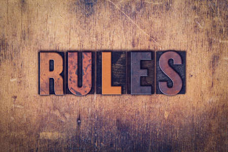 precedent: The word Rules written in dirty vintage letterpress type on a aged wooden background.