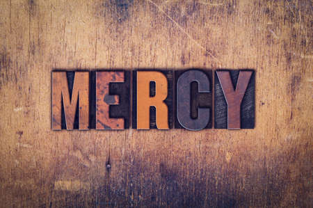 pity: The word Mercy written in dirty vintage letterpress type on a aged wooden background. Stock Photo