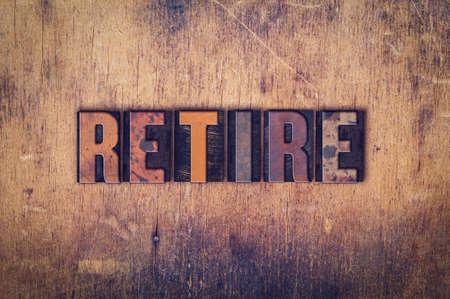 retire: The word Retire written in dirty vintage letterpress type on a aged wooden background.