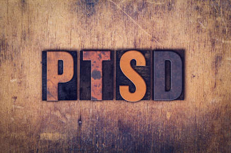 traumatic: The word PTSD written in dirty vintage letterpress type on a aged wooden background.