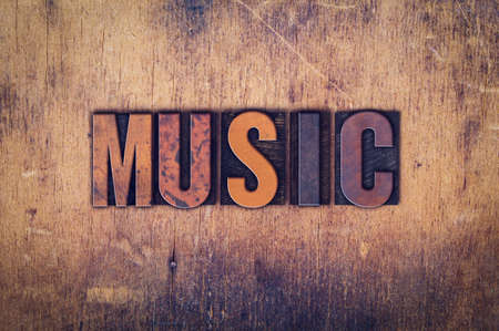 hymn: The word Music written in dirty vintage letterpress type on a aged wooden background. Stock Photo