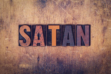 antichrist: The word Satan written in dirty vintage letterpress type on a aged wooden background. Stock Photo