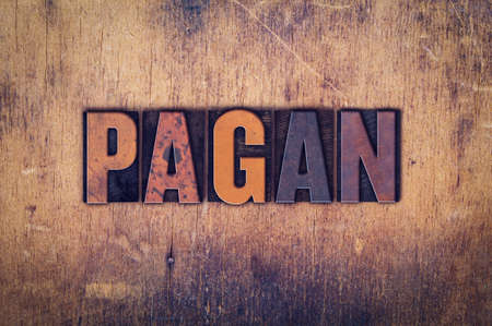 pagan: The word Pagan written in dirty vintage letterpress type on a aged wooden background.