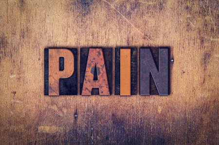 pain killers: The word Pain written in dirty vintage letterpress type on a aged wooden background.