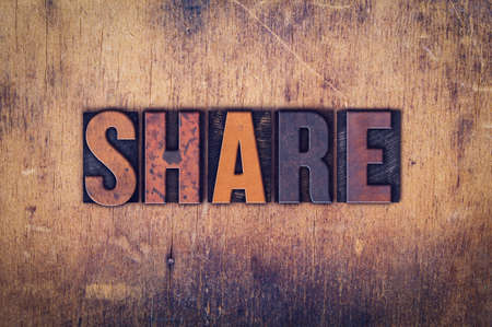 shared sharing: The word Share written in dirty vintage letterpress type on a aged wooden background.