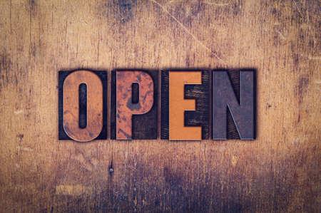 """Het woord """"Open"""" geschreven in vuile vintage boekdruk type op een leeftijd houten achtergrond."""