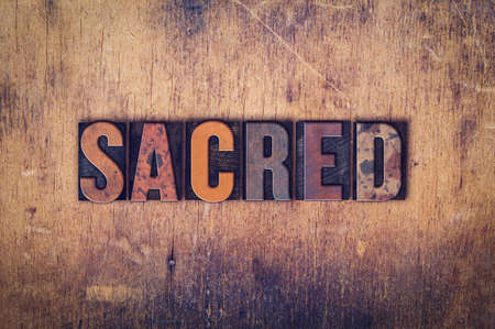 hallowed: The word Sacred written in dirty vintage letterpress type on a aged wooden background.