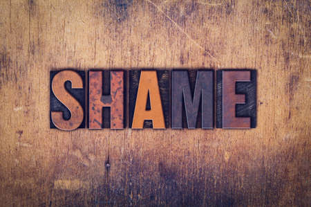 disgrace: The word Shame written in dirty vintage letterpress type on a aged wooden background. Stock Photo