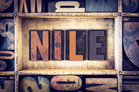 letterpress type: The word Nile written in vintage wooden letterpress type.