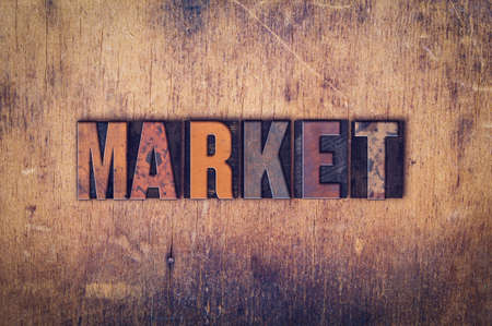 advertise: The word Market written in dirty vintage letterpress type on a aged wooden background.