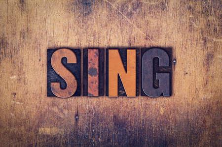 """letras musicales: La palabra """"Sing"""", escrita en el tipo de cosecha sucio en un fondo de madera envejecida."""