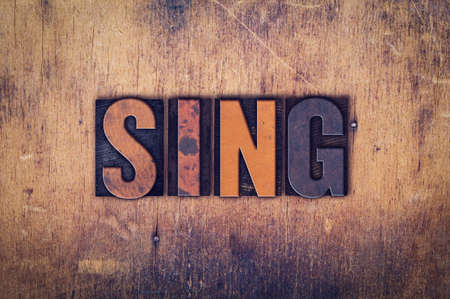 chorale: The word Sing written in dirty vintage letterpress type on a aged wooden background.