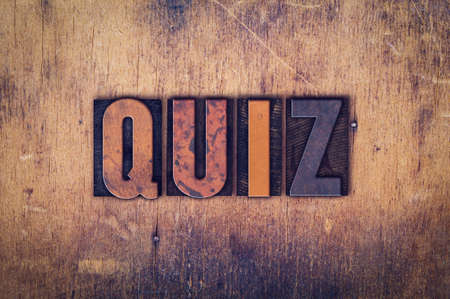 trivia: The word Quiz written in dirty vintage letterpress type on a aged wooden background.