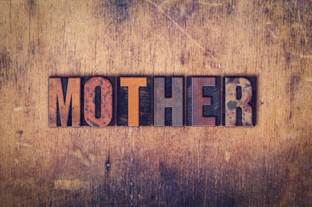 matron: The word Mother written in dirty vintage letterpress type on a aged wooden background.