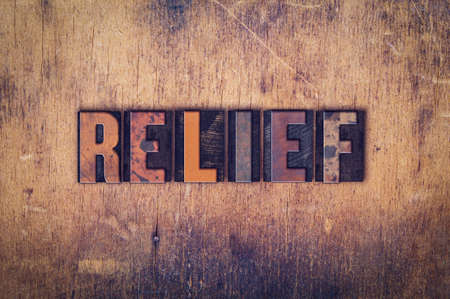 respite: The word Relief written in dirty vintage letterpress type on a aged wooden background.