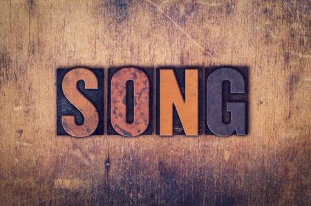 """letras musicales: La palabra """"Canción"""", escrita en el tipo de tipografía de la vendimia sucia en un fondo de madera envejecida."""