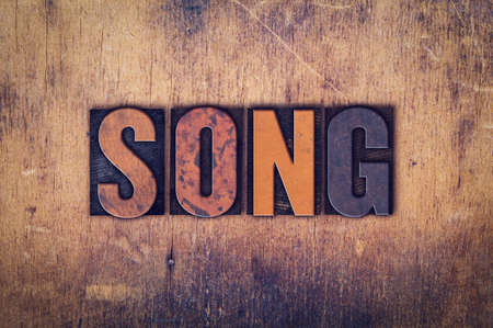 The word Song written in dirty vintage letterpress type on a aged wooden background.