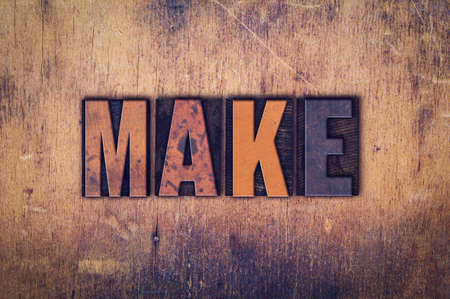 devise: The word Make written in dirty vintage letterpress type on a aged wooden background. Stock Photo
