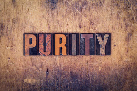 unblemished: The word Purity written in dirty vintage letterpress type on a aged wooden background.