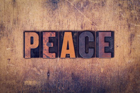 ceasefire: The word Peace written in dirty vintage letterpress type on a aged wooden background.