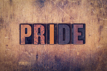 The word Pride written in dirty vintage letterpress type on a aged wooden background.